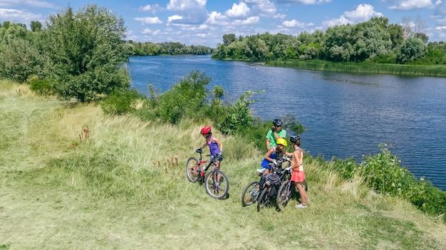 Familie op fietsen buiten fietsen, actieve ouders en kinderen op fietsen, luchtfoto bovenaanzicht van gelukkige familie met kinderen ontspannen in de buurt van prachtige rivier van bovenaf, sport en fitness concept