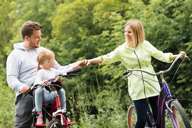 Familie op fietsen die handen houden