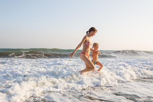 Familie op het strand bij zonsondergang. moeder en dochter lopen samen.