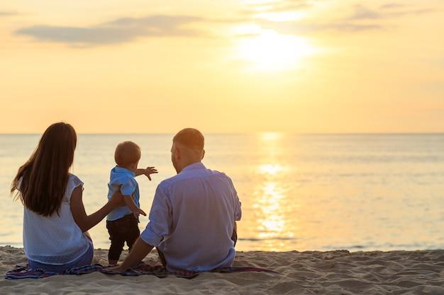 Familie op het strandconcept, kaukasische jongen die en zand op het tropische strand in zonsondergangtijd situeert houdt