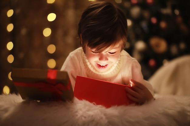 Familie op kerstavond bij open haard. kinderen openen kerstcadeautjes. kinderen onder de kerstboom met geschenkdozen. ingerichte woonkamer met traditionele open haard. gezellige warme winteravond in huis.