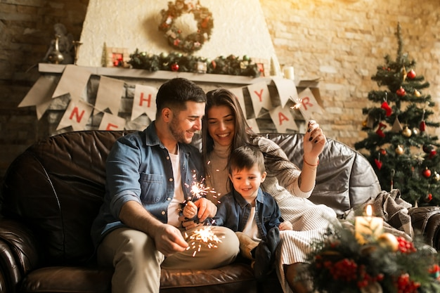 Familie op kerstmis met de lichten van bengalen