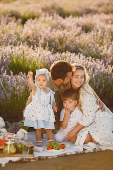 Familie op lavendelveld. mensen op een picknick. moeder met kinderen eet fruit.