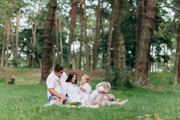 Familie op picknick. moeder, vader en dochtertje zittend op een deken in het park. het concept van de zomervakantie. moederdag, vaderdag, baby's dag. samen tijd doorbrengen. familie-look