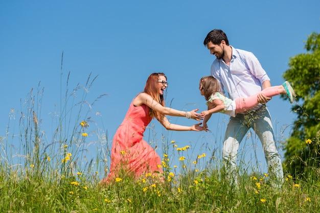 Familie op weide spelen met hun dochtertje