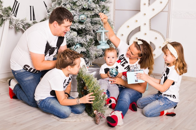 Familie opening kerstcadeautjes thuis samen.