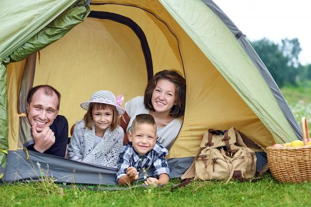 Familie ouders en twee kinderen in kampeertent. gelukkig moeder, vader, zoon en dochter op zomervakantie