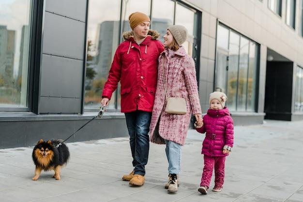 Familie, ouderschap en mensen concept-gelukkige moeder, vader en meisje wandelen in de herfst stad en plezier hebben.