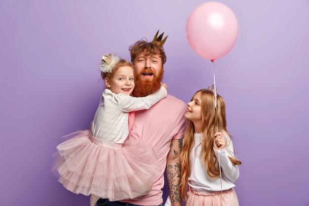 Familie-, ouderschap- en vakantieconcept. grappige vader entertaint kinderen, draagt kleine dochter op handen, versier kamer voor feest, draag feestelijke kleding, geïsoleerd over paarse muur.