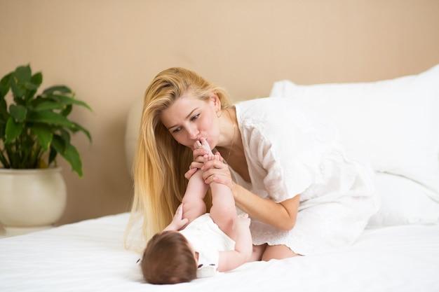 Familie, ouderschap ochtend concept. gelukkige baby met moeder in bed thuis