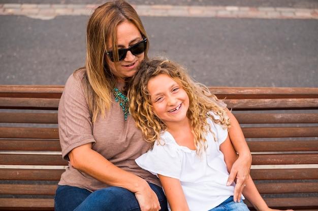Familie paar moeder en dochter samen in de buitenlucht gelukkig vrijetijdsbesteding knuffelen en genieten van de dag van de zomer voor de terug naar school en de winter. blonde blanke moeder en meisje
