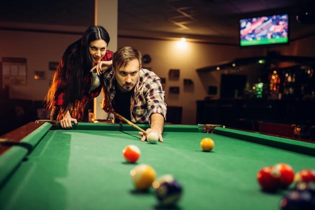 Familie paar speelt in biljartkamer. man en vrouw vrije tijd, amerikaans poolspel in sportbar, mannelijke speler die naar schot streeft