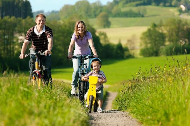 Familie paardrijden fietsen in de zomer