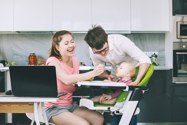 Familie pappa en mamma voeden baby in de keuken gelukkig samen thuis lachend in de keuken