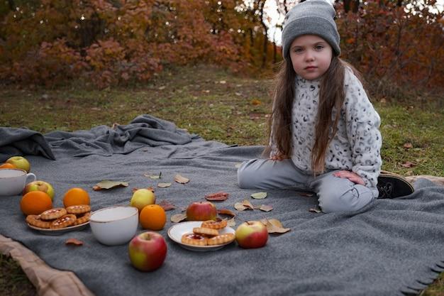 Familie picknick in een herfst gouden tijd. moeder met meisje dat warme chocolademelk of thee buiten drinkt in het herfstseizoen.