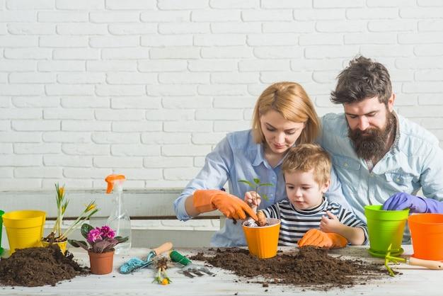 Familie planten tuinieren familie planten bloemen zoon helpt moeder om voor planten te zorgen tuinieren