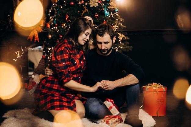 Familie portret. charmant paar van zwangere vrouw in geruit overhemd en knappe man poseren in een gezellige