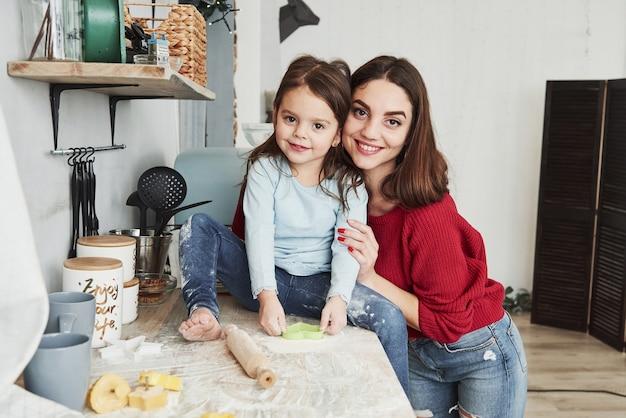 Familie portret. moeder en dochter hebben plezier in de keuken.