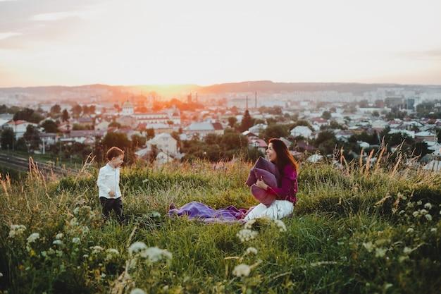 Familie portret. natuur. moeder speelt met een zon waarin kussens in zitten