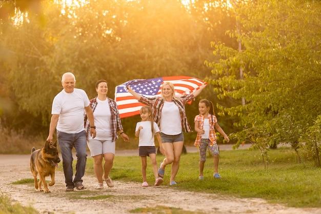 Familie poseren buiten met amerikaanse vlag