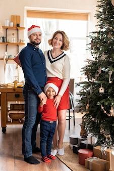 Familie poseren naast kerstboom