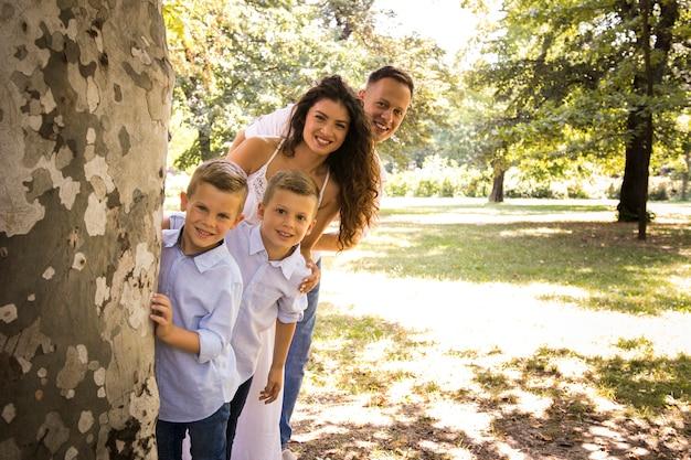 Familie poseren voor de camera achter een boom