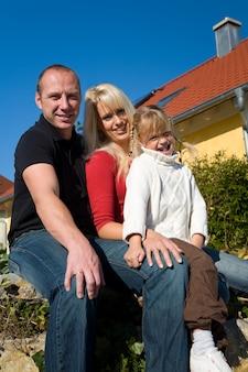 Familie poseren voor een huis
