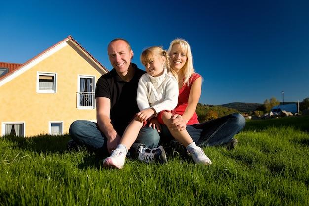Familie poseren voor hun huis