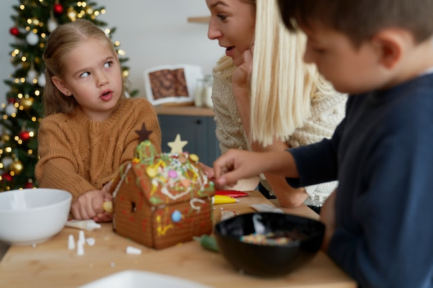 Familie praten tijdens het versieren van peperkoek huis