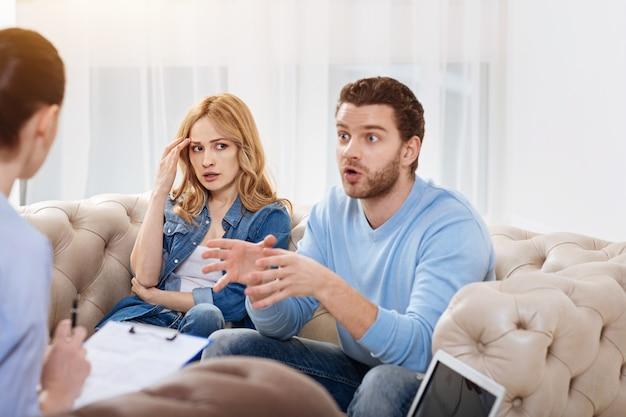 Familie problemen. emotionele bebaarde jongeman zit naast zijn vrouw en vertelt de therapeut over hun gezinsproblemen terwijl hij een afspraak heeft met een psycholoog