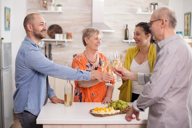 Familie rammelende glazen van meerdere generaties met wijn in de keuken van het huis tijdens de reünie.