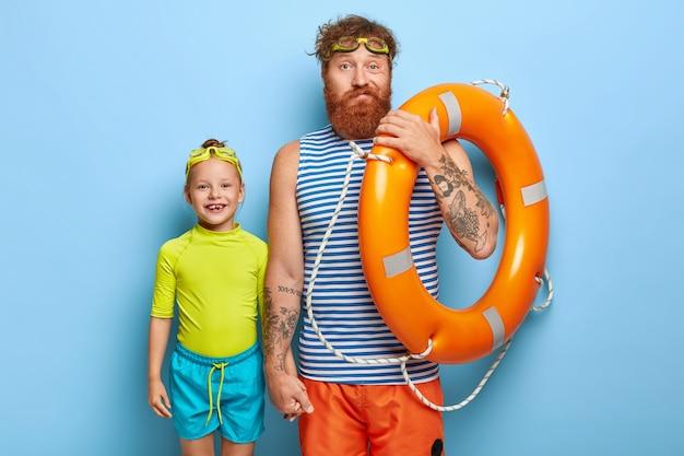 Familie recreatie. bebaarde gember vader houdt hand van kleine dochter, gekleed in zomeroutfit, houdt zwemuitrusting vast, brengt zomervakantie door aan zee, geïsoleerd op blauwe muur, zoals dit seizoen