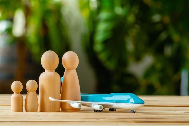 Familie reizen en vakantie concept. houten figuren van familie en speelgoed vliegtuig