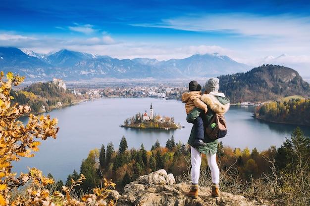 Familie reizen europa. moeder met zoon op zoek op het meer van bled. herfst of winter in slovenië, europa. bovenaanzicht op eiland met katholieke kerk in het meer van bled met kasteel en bergen op de achtergrond.