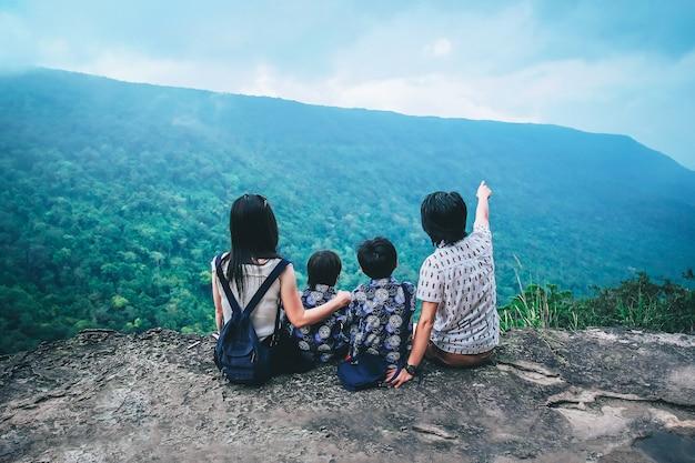 Familie reiziger op zoek naar uitzicht op de natuur op de top van de berg.