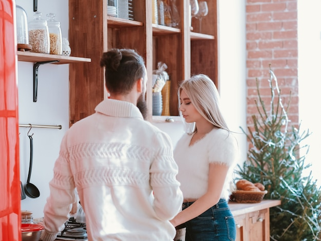 Familie relatie. man met serieus gesprek met zijn vrouw in de moderne keuken. groene dennenboom erin.