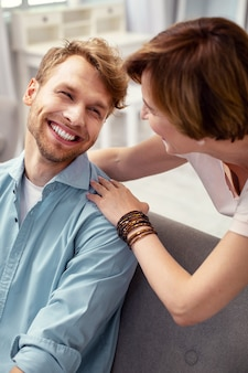 Familie relaties. gelukkig positieve man die lacht naar zijn moeder terwijl ze haar zorg nodig heeft