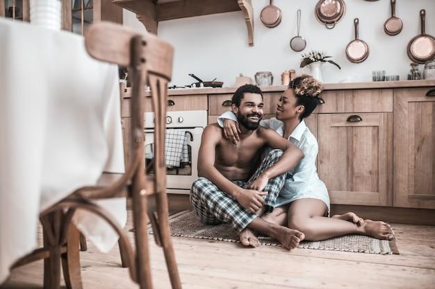 Familie relaties. vrolijke afro-amerikanen man en vrouw zittend op tapijt op de vloer knuffelen communiceren