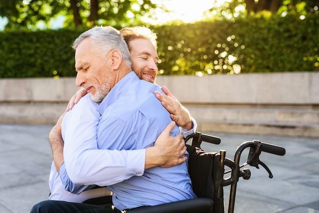 Familie relaties. zoon knuffels gelukkige oude man.