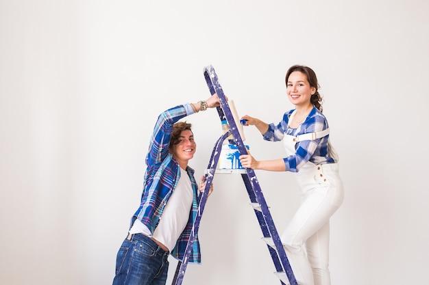 Familie, renovatie, geluk en herinrichting concept - jong gezin doet reparatie, samen muren schilderen en lachen