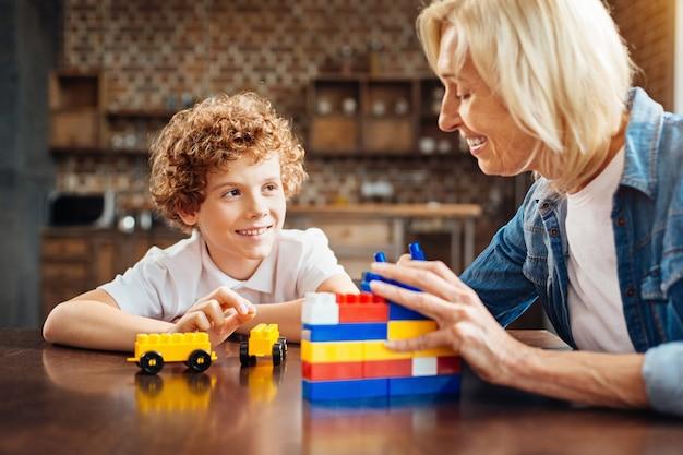 Familie roddels. selectieve aandacht voor een vrolijke jongen die met een brede glimlach naar zijn gelukkige oma kijkt terwijl hij allebei met een bouwdoos speelt
