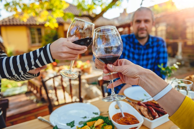 Familie roosteren tijdens de lunch in de achtertuin patio