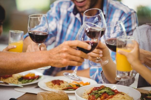 Familie roosterende glazen wijn op eettafel terwijl het hebben van een maaltijd