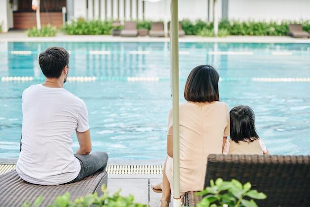 Familie rusten bij zwembad