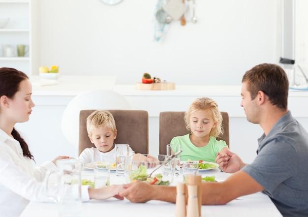 Familie samen bidden voor het eten van hun salade voor de lunch