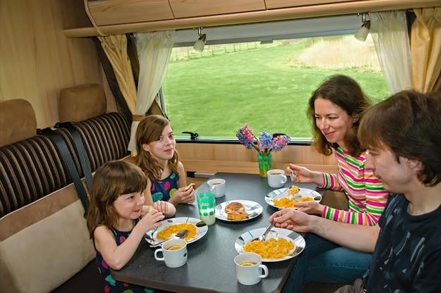 Familie samen eten in rv interieur ouders en kinderen reizen in camper caravan