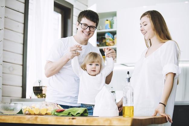 Familie samen gelukkig jong mooi met een klein kind diner in de keuken thuis voorbereiden