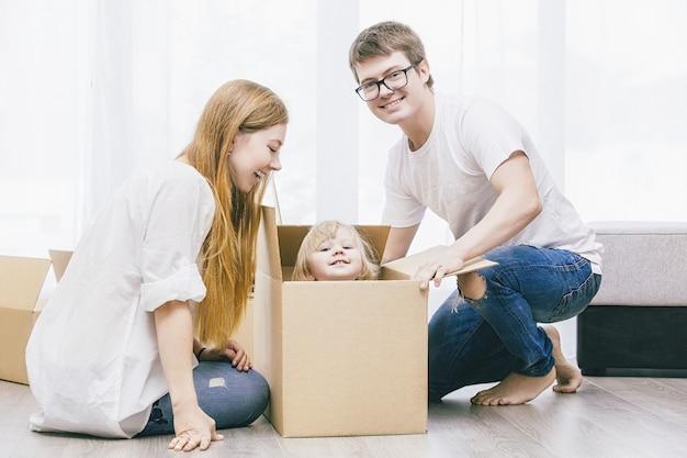 Familie samen gelukkig jong mooi met een kleine baby verhuist met dozen naar een nieuw huis