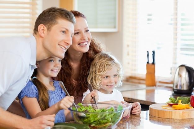 Familie samen met salade in de keuken