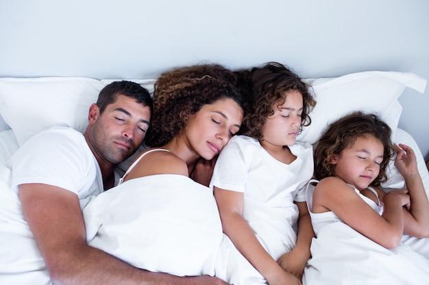 Familie samen slapen op bed
